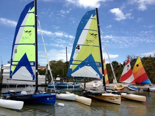 Trimarans and Sunfish Sailboats in a row